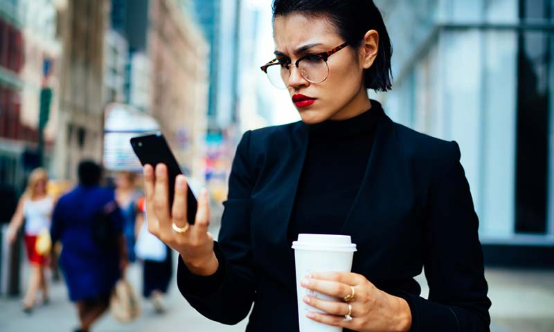 A woman checking email on her phone and she has a distrusting look on her face.
