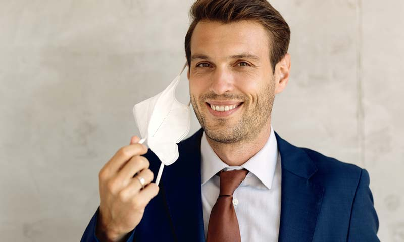 A happy business man removing his mask